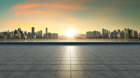 Empty concrete tiles floor with city skyline background. Sunset scene 免版税图像