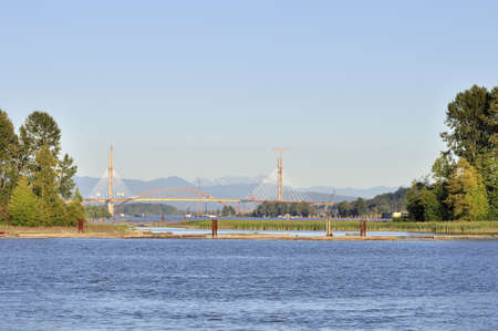 Fraser River with Trees on an Island and a Bridge under Construction photo