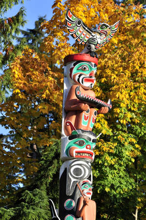 the totem pole: Totem in the park with fall foliage on the background   Stock Photo