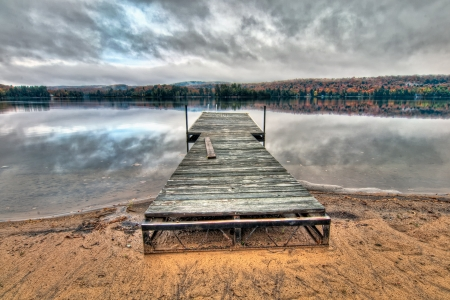 Dock in the middle of a lake with reflection of dramatic clouds