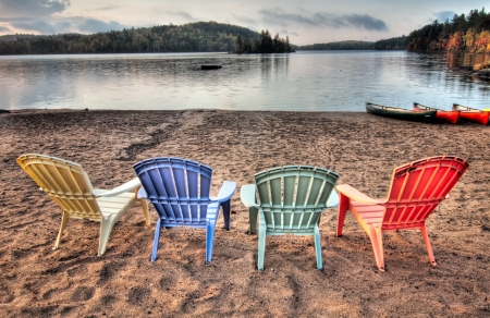 Four colorful patio chairs overlooking a lake with Canoes along the shore  Stock Photo