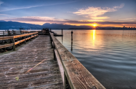 Pier moving out to the water while sun star rises over the mountain Stock Photo