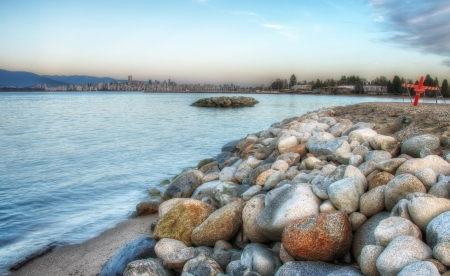 Vancouver skyline can be seen in the distance with rocks, pylons and water in the foreground