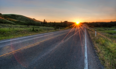 This road vanishes to the distance with a sun star and grass along the roadside   HDR is used to maintain details and some flare left in to maintain realism