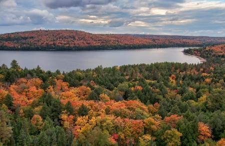 Bekijk of Rock meer wijzend in de verte met Herfst bomen wisselende kleuren rond het meer