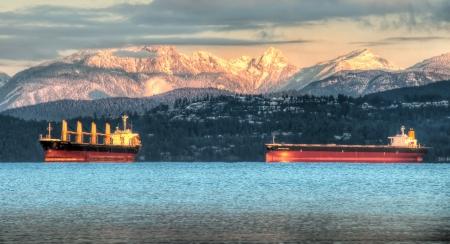 Deze bevatten schepen zitten net voor de kust van Vancouver onder de witte besneeuwde kust-berg op de achtergrond