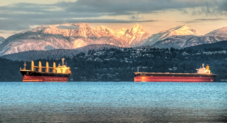 These contain ships sit just off the coast of Vancouver below the white snowy coastal mountain in the background