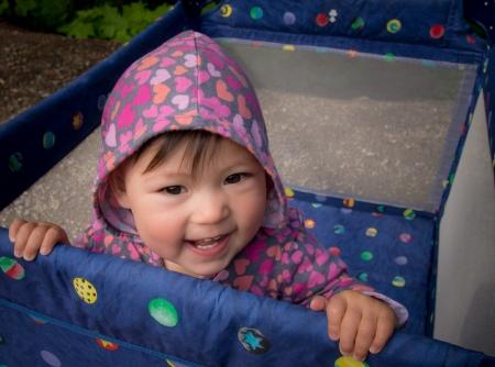 Deze multi-raciale baby baby is gelukkig in een box buiten.