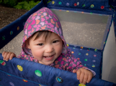 This multi racial baby baby is happy in a playpen outside.