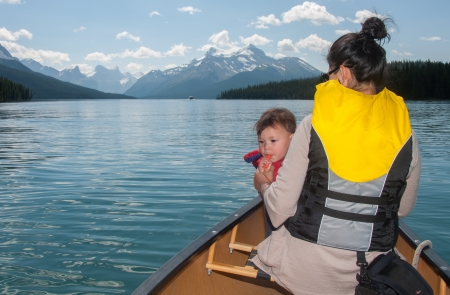 Mixed race baby is blowing a whistle in a canoe with her mother. Stock Photo