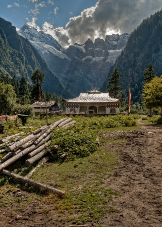 tibetan house: Tibetan house with mountains in the background which is the trail head for the hike to the Yubeng sacred waterfall in Meili mountain