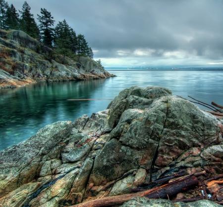 Koele toon foto langs een rotsachtige kust met de Vancouver skyline van de stad in de verte