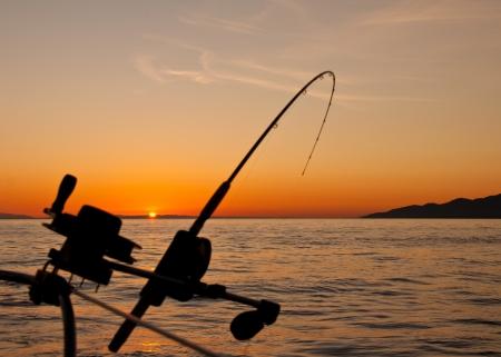 barca da pesca: Preso al largo della costa dell'isola di Vancouver la silhouette di una canna da pesca sartiame gi� al tramonto Archivio Fotografico