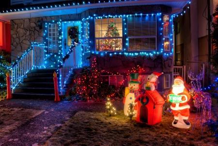 Huis versierd met kerstverlichting en ornamenten in de voorkant gazon