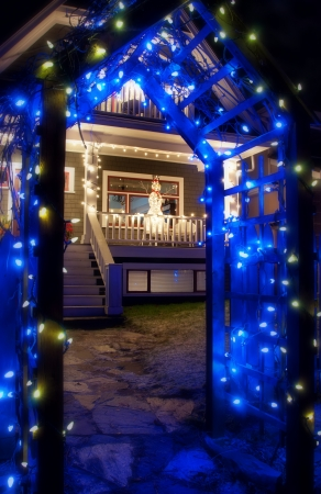 Blue Christmas Light Archway in front of house with snowman Stock Photo