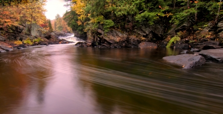 Flowing river with fall colors in the distance