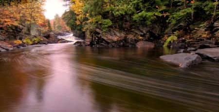 Stromende rivier met herfstkleuren in de verte