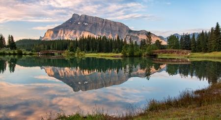 Rundle berg weerspiegeld in vijver met twee bruggen