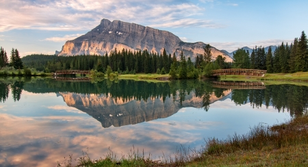 banff national park: Rundle mountain reflected in pond with two bridges