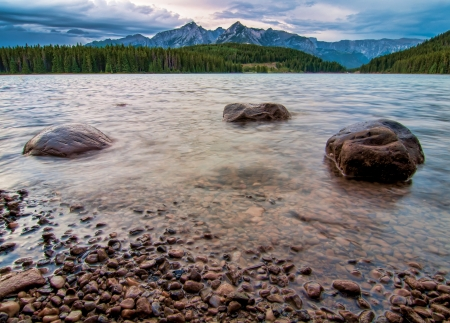 Three rocks in a ripply lake with forest and mountain peaks in the distance  photo