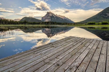 Wooden dock beside Vermilion lakes with perfect mountain reflection