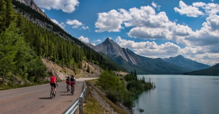 Three cyclists on a road in Jasper national park with a mountain peak in the distance