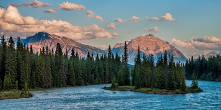 Photo of the mountains and forest behind the Athabasca River in Jasper National Park  Stock Photo