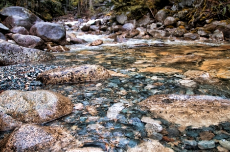 Stream with clear water and closeup of large and small rocks
