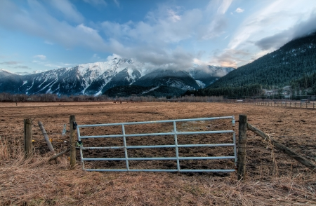 Fence gate for a farm pasture with snowy mountains in background