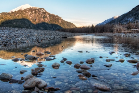 Clear river with rocks leads towards mountains lit by sunset