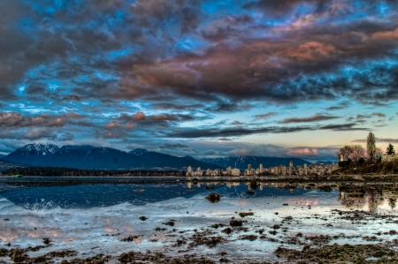 Reflection of Vancouver skyline and dramatic blue sky