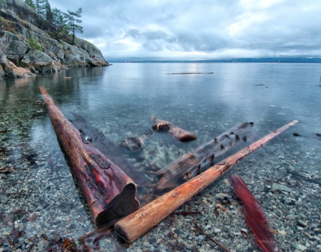 Log in V-shape along coast with Vancouver skyline in far  Stock Photo
