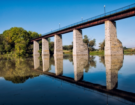 Historic railroad trestle over river with reflection in the river