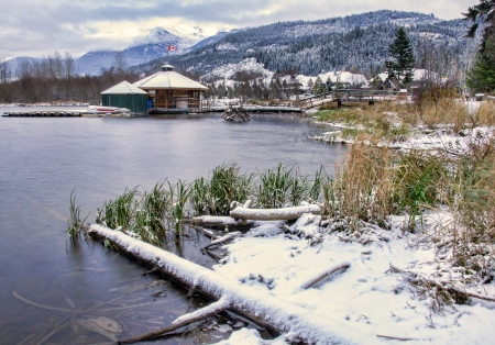 Lake with snow along shore and building floating on lake
