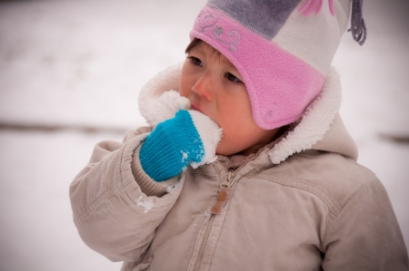 Toddler eating snow with cute mittens and hat photo