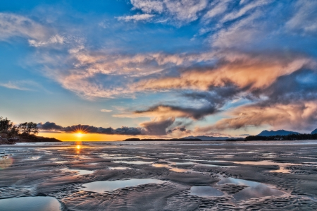 Pools of water in sand and dramatic sunset Stock Photo