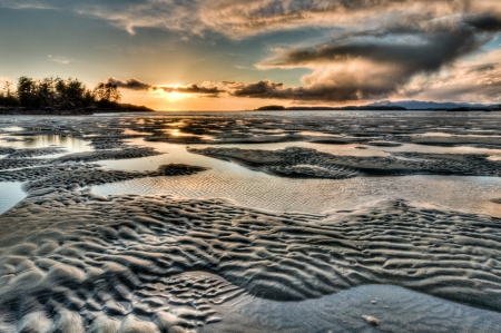 Rippled sand and water beach sunset