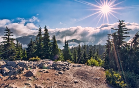 On top of mountain a sun star above the clouds Stock Photo