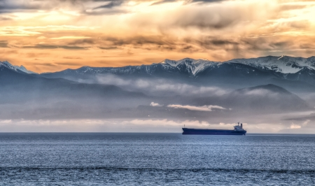 british columbia: One Transport Ship with mountains and orange sky in background