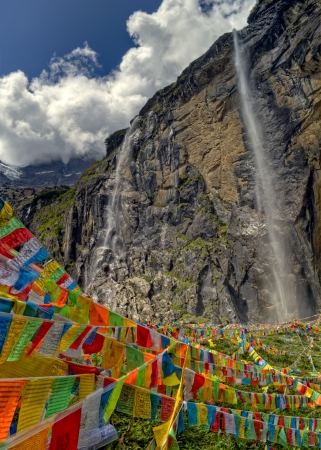 Sacred Buddhist Waterfall with colorful prayer flags in Yubeng, Yunnan, China  photo