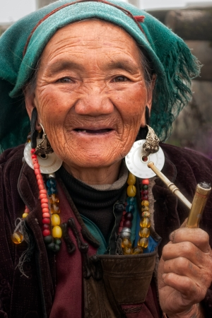 An old Tibetan woman smoking with a pipe