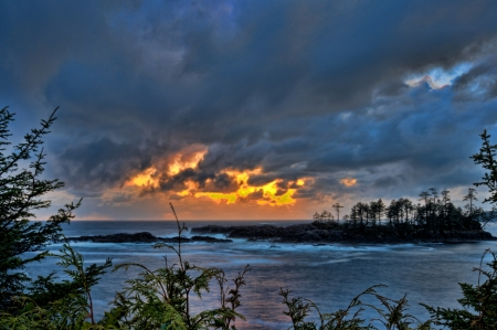 Rough ocean with storm clouds from golden sunset above Stock Photo