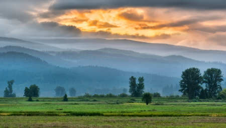 british columbia: Orange sunrise over the foothills of a mountain Stock Photo