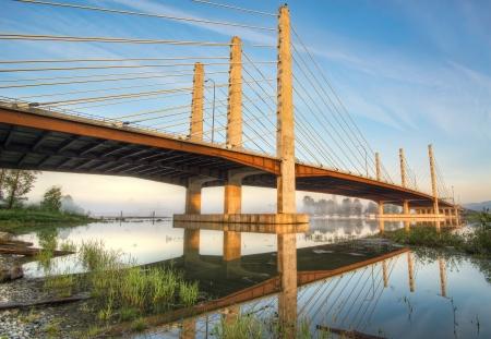 Full reflection of a golden lit bridge Archivio Fotografico