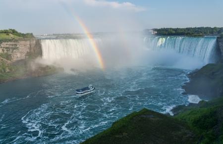 Regenboog bij de Niagara Falls met boot