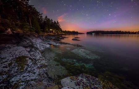 Purple night sky along rocky coast