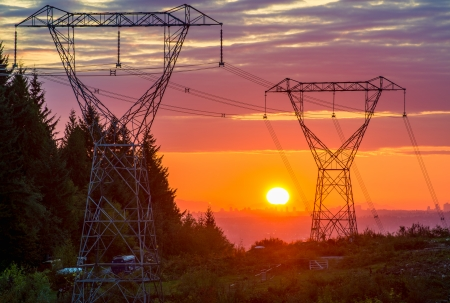 Sunset behind large power line towers Stock Photo