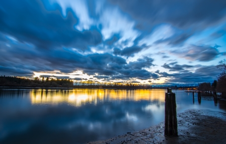horizon over water: Motion blur of blue clouds over river at sunset