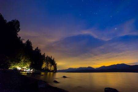 Camping in tents next to lake with Blue and Orange night sky