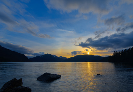 Sun setting behind mountains over lake  Stock Photo